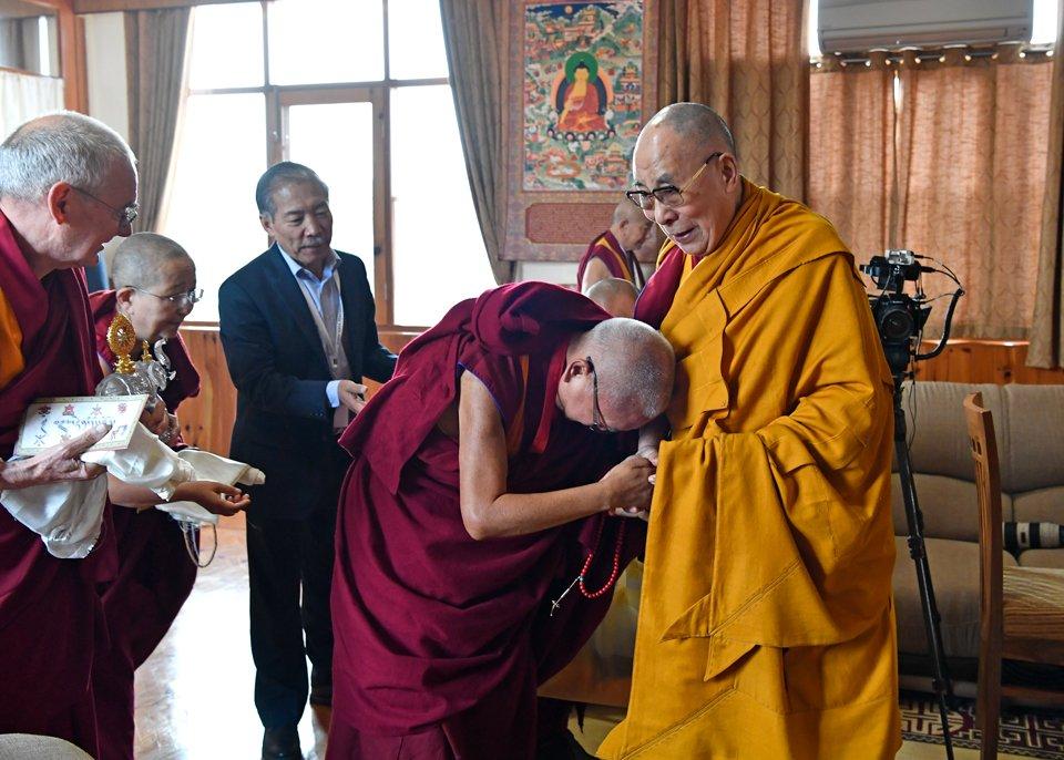 Lama Zopa Rinpoche bowing deeply to His Holiness the Dalai Lama
