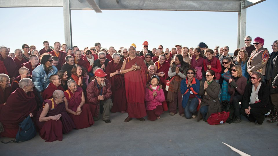 Lama Zopa Rinpoche surrounded by students in a construction site