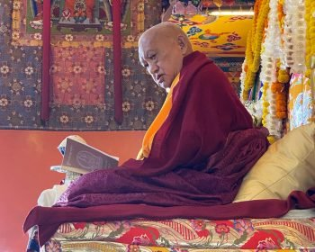 Lama Zopa Rinpoche seated on throne looking at a prayer book