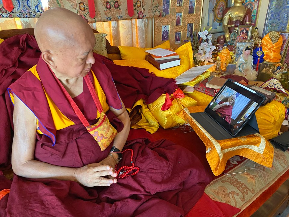 Lama Zopa Rinpoche seated and watching His Holiness teaching on his iPad