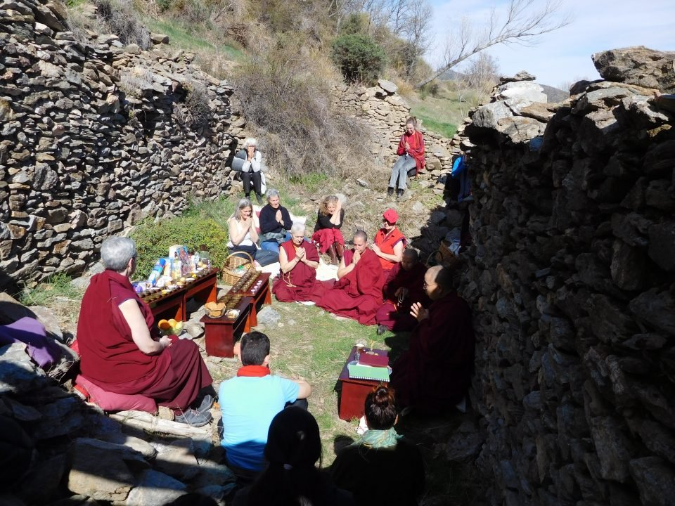 ordained sangha and students doing puja among old stone ruins