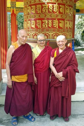 Two monks and a nun standing in front of a prayer wheel posing for the camera.