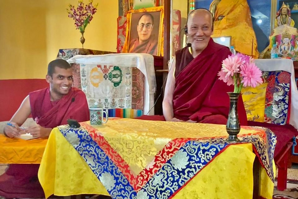 Two monks seated behind tables in the front of a gompa smiling.