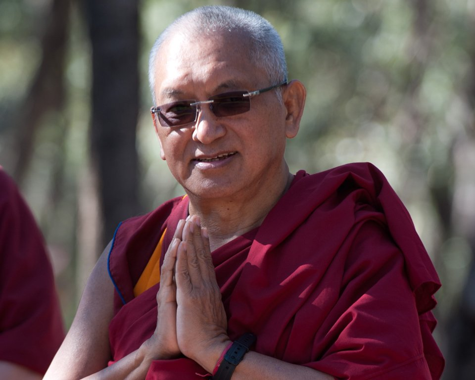 Lama Zopa Rinpoche looking at the camera with hands in prostration mudra and smiling