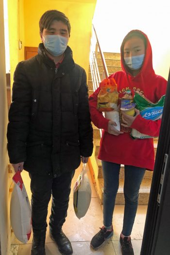 Two young people wearing face masks standing in a doorway holding bags of food.