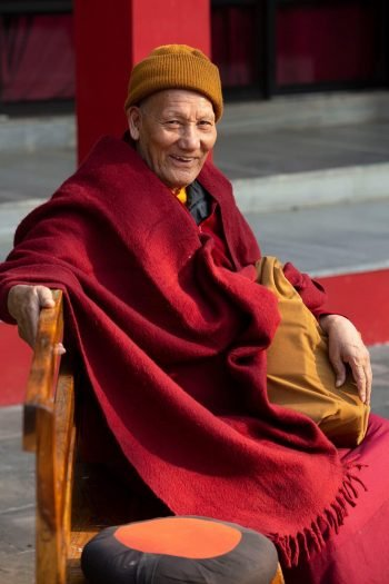 An older monk seated on a wood bench outside looking into the camera and smiling.