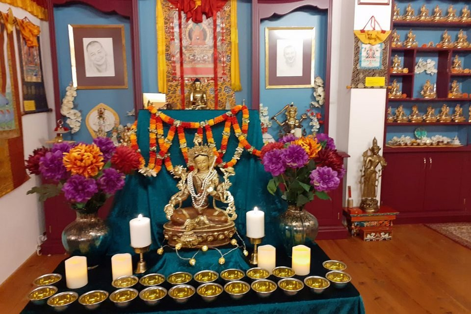Golden Tara statue on a table with water bowls and candles and flowers inside of a colorful room.