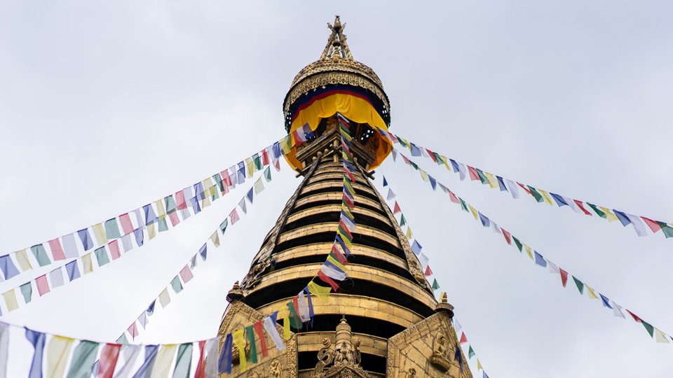 view of top levels of stupa with prayer flags