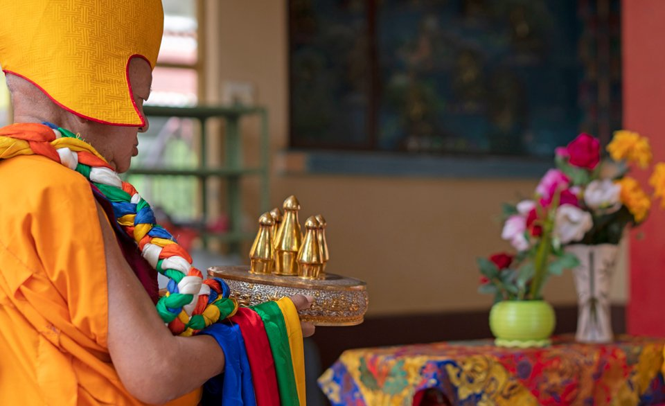Lama Zopa Rinpoche in a yellow hat offering a gold mandala in profile
