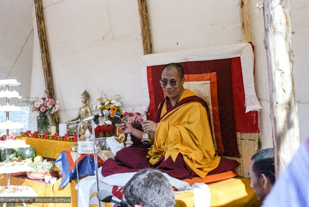 archive photo of His Holiness the Dalai Lama under a tent doing puja