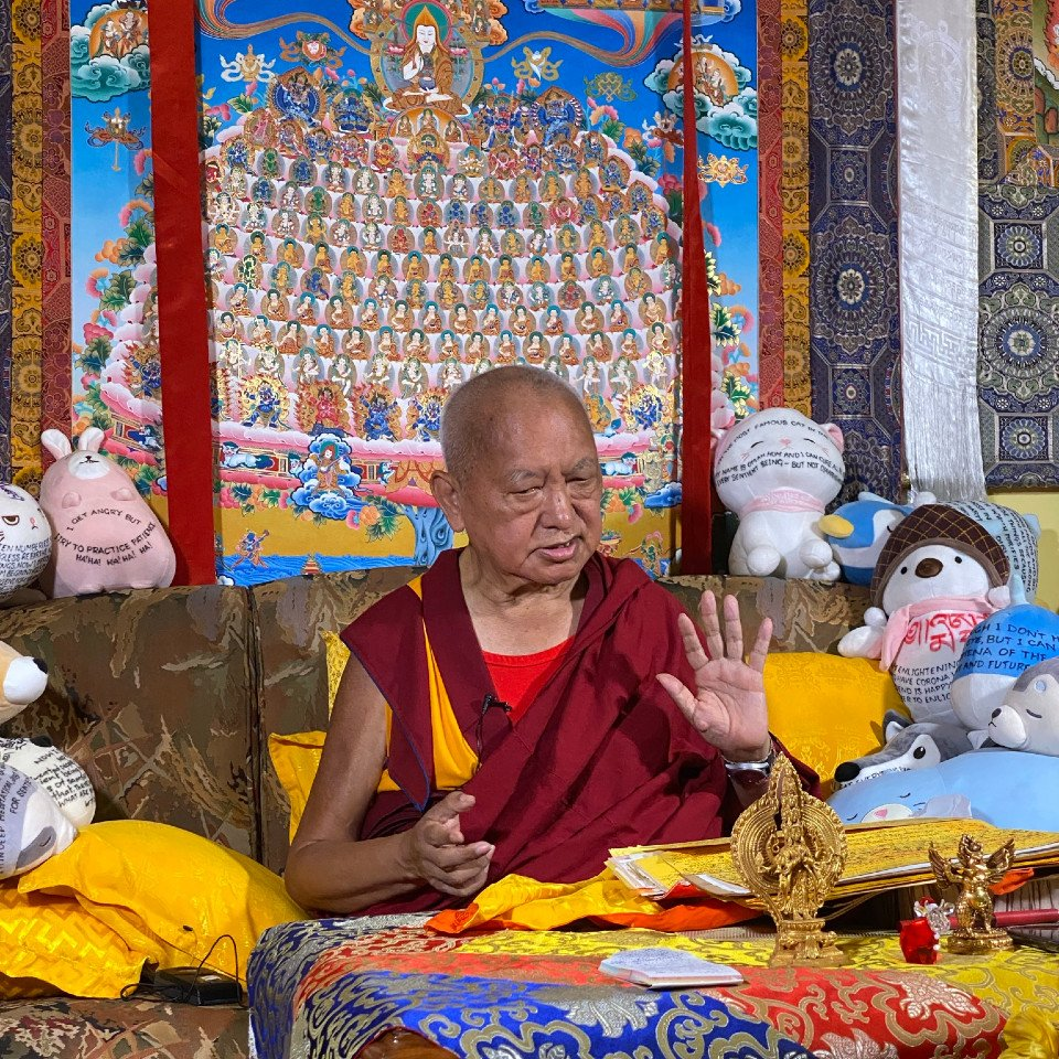 Lama Zopa Rinpoche seated in front of large merit field thangka