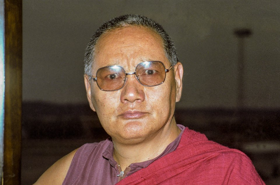 Head shot of Lama Yeshe staring directly at the camera through tinted glasses