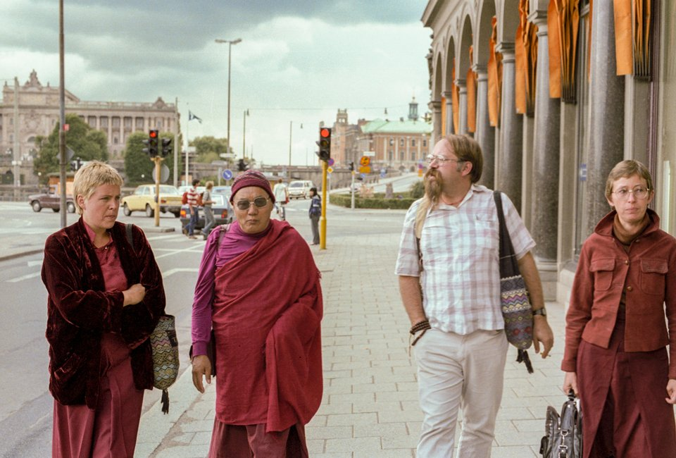 Lama Yeshe walking down the street in Stockholm with three Western students, two of whom are wearing robes.