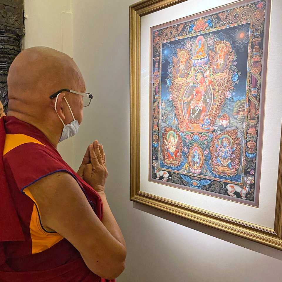 Rinpoche stands with hands folded an looks at framed image of a deity