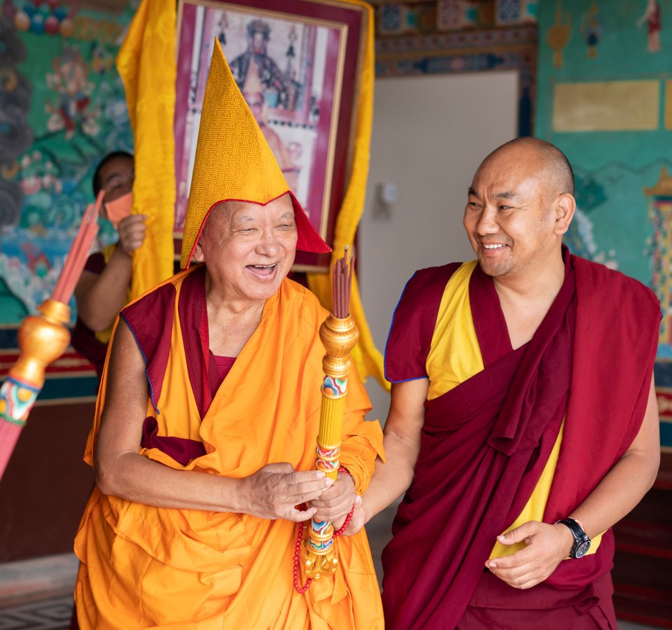 Lama Zopa Rinopche leading a large photo of His Holiness the Dalai Lama in the enterance to the Kopan Monastery gompa