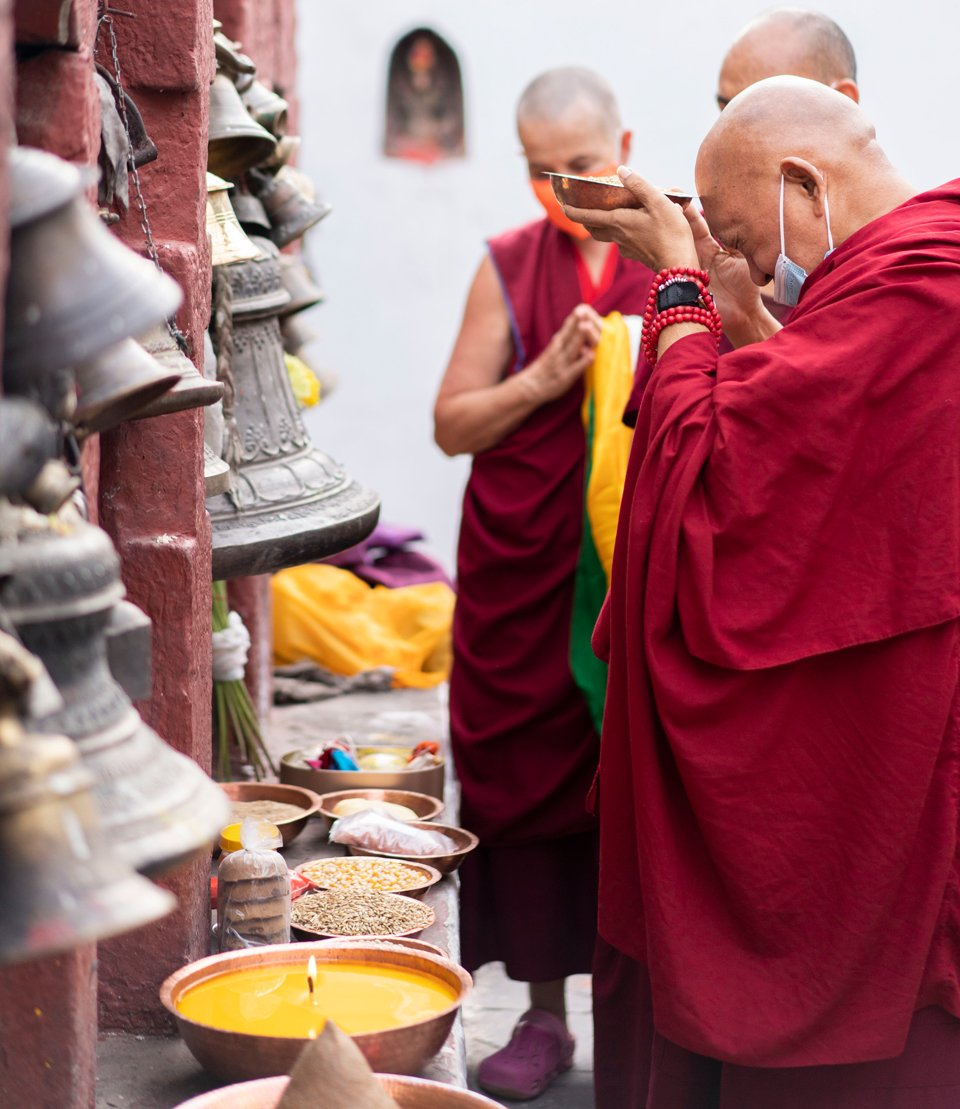 Rinpoche holding up an offering in front of other offerings and bells
