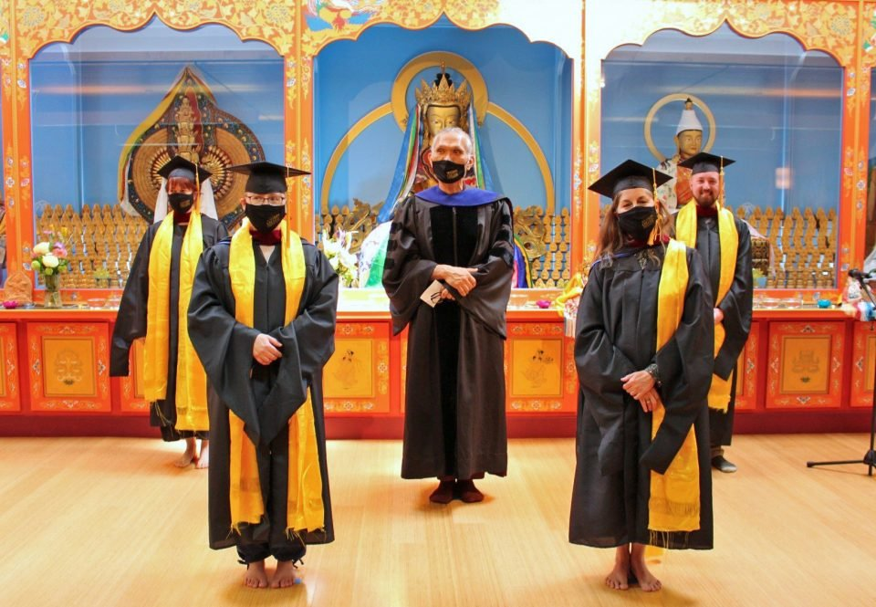 Four graduates in graduation gowns caps and face masks standing alongside their teacher dressed in commencement gown and face mask.