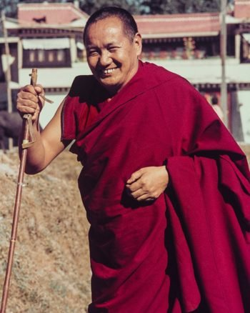 Lama Yeshe in robes walking with a ski pole with the gompa building in the background