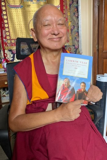 Lama Zopa Rinpoche smiling and holding up a book
