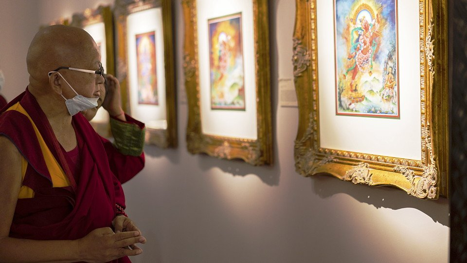 Rinpoche looking at framed images of Buddhist deities