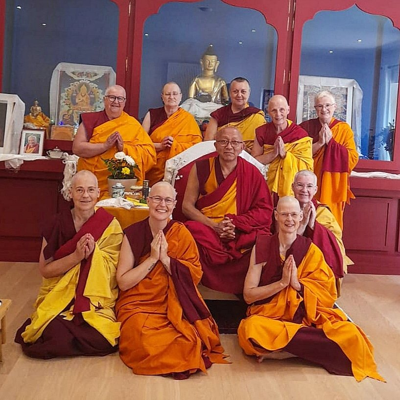 Nine nuns surround a geshe monk in front of a large altar