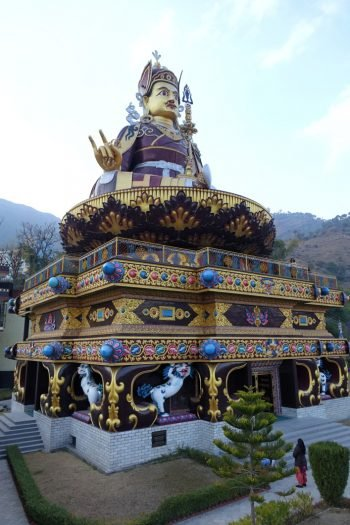 Very large gold statue of Padmasambhava on intricate throne, which is also a building with a person in the foreground looking at the towering statue and with foothills in the background