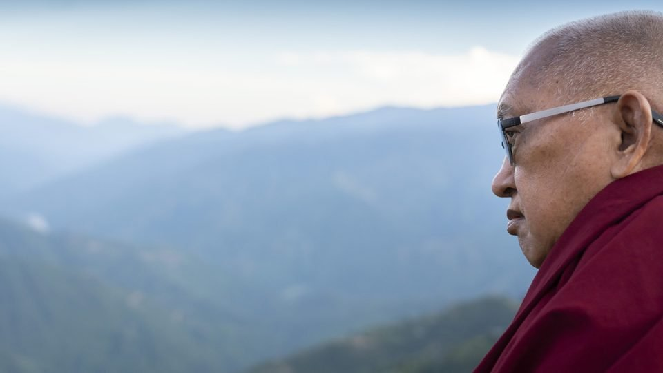 Lama Zopa Rinpoche in profile looking over a valley and foothills