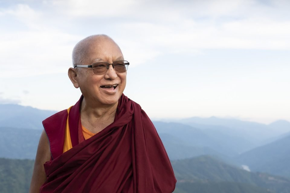 Lama Zopa Rinpoche smiling and standing outside on a hill overlooking foothills in the background