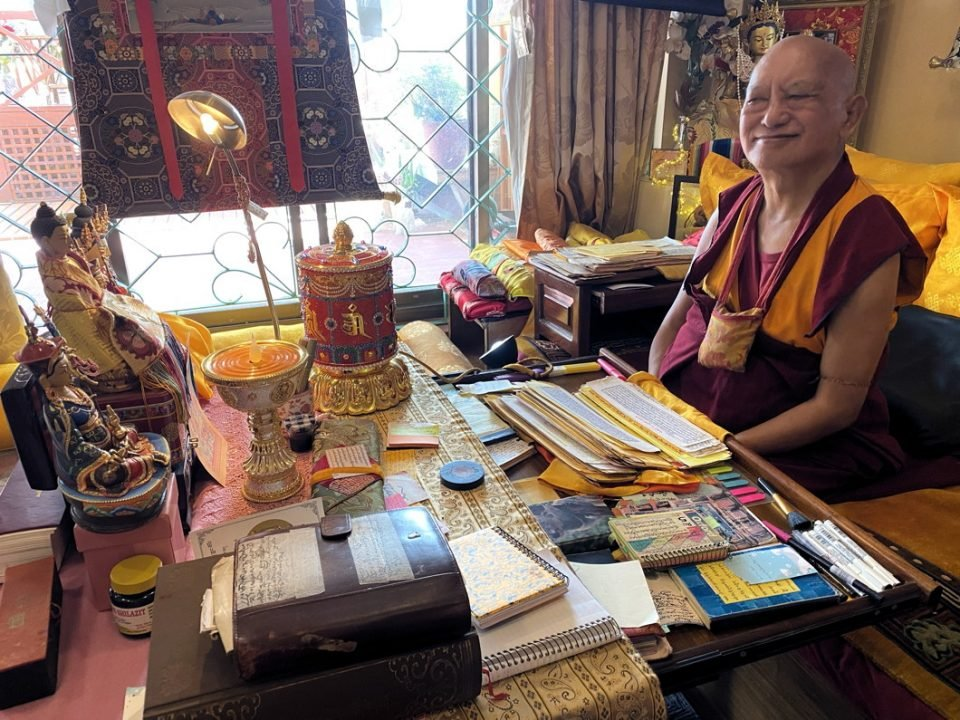Lama Zopa Rinpoche smiling sitting next to a table full of texts and holy objects