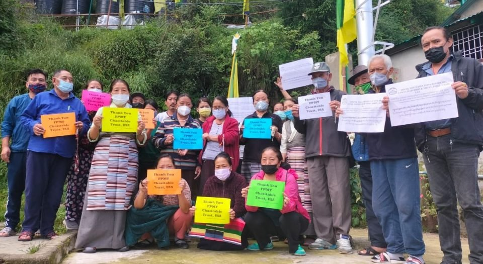 Tibetan refugees stand with notes of thanks for FPMT Charitable Projects.