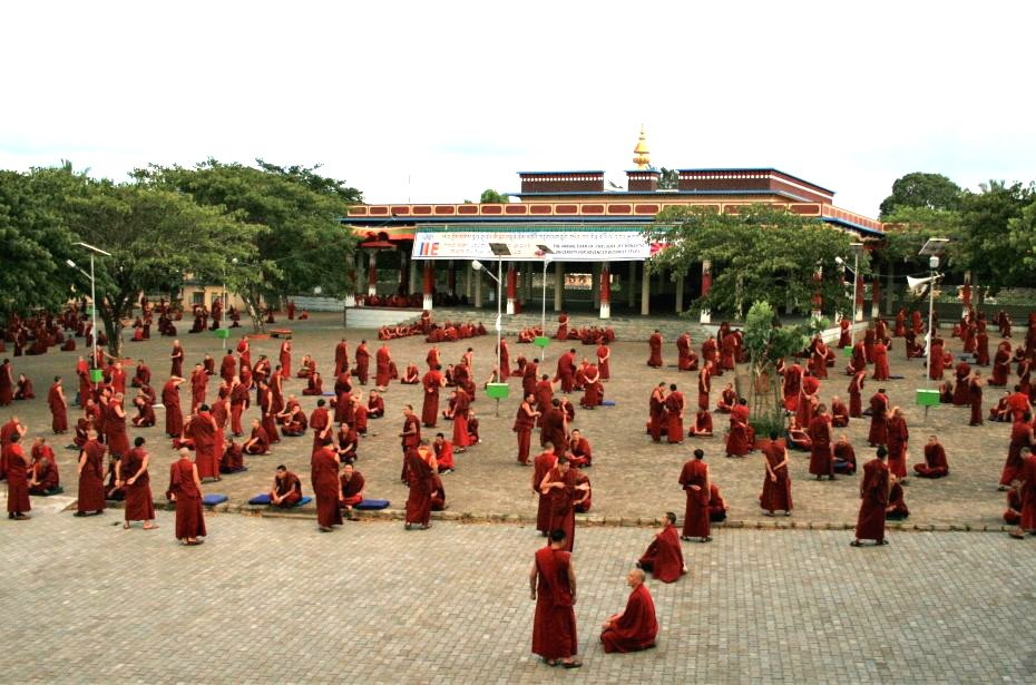 Many red robed monks debating in large courtyard