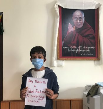 Tibetan man standing with a thank you note next to a picture of His Holiness the Dalai Lama.