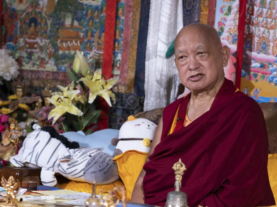 Lama Zopa Rinpoche seated on a couch with a Merit Field thangka and stuff animals behind him