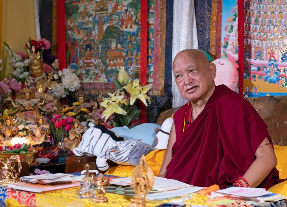 Lama Zopa Rinpoche seated on a couch with a Merit Field thangka, statues, flowers, and stuff animals behind him