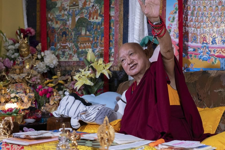 Lama Zopa Rinpoche gesturing with his arm during the recording of a video teaching with flowers, thangkas, and stuffed animals with Dharma messages written on them in the background.