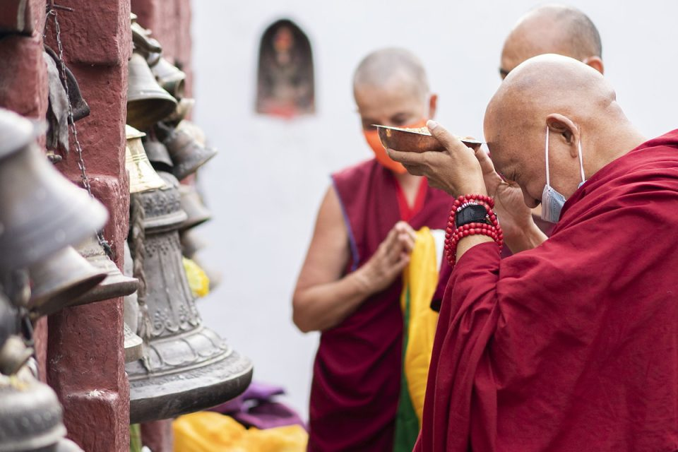 Lama Zopa Rinpoche holding a full offering bowl to his forehead while making prayers with bells visible and a nun with folded hands and khatas in the background