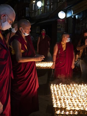 Lama Zopa Rinpoche praying over hundreds of butter lamp offerings at night