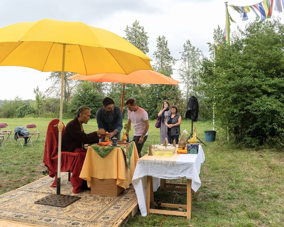 Yangsi Rinpoche sitting under a yellow umbrella outside with a few students
