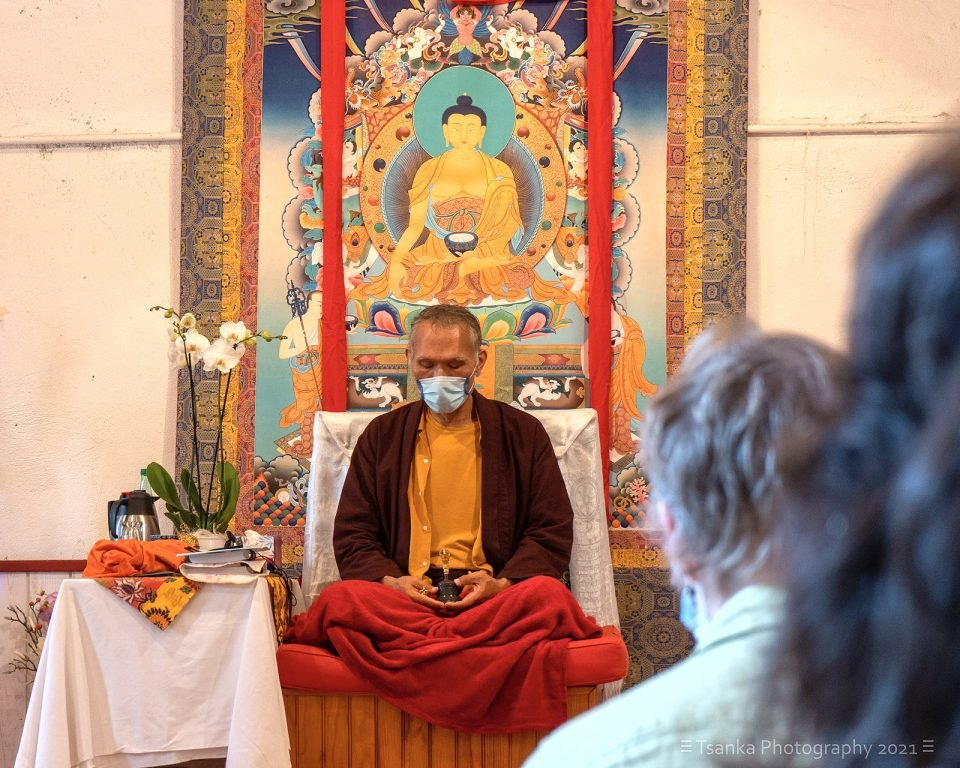 Yangsi Rinpoche sits on an informal throne in front of a large thangka