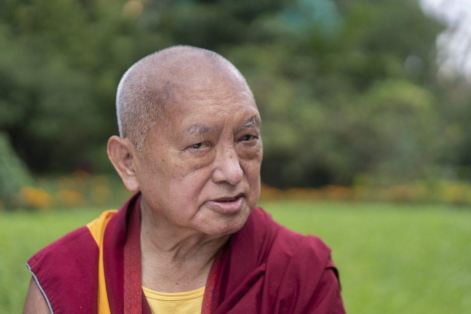 Lama Zopa Rinpoche talking in a green garden