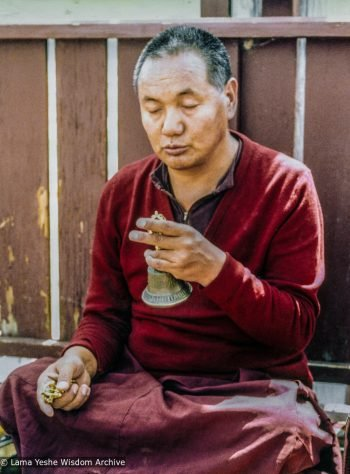 Lama Yeshe seated with legs crossed and eyes closed, holding a dorje and bell