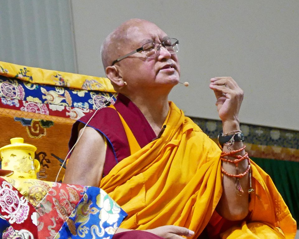 Lama Zopa Rinpoche teaching on the throne. Rinpoche's eyes are closed and he is gesturing with his hand.