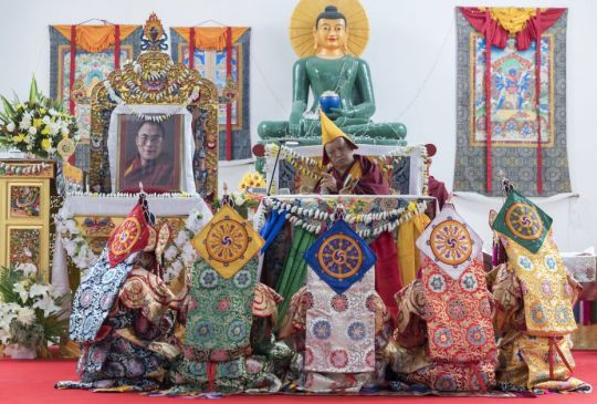 Lama Zopa Rinpoche presiding over Lama Chöpa. Thefivedakinis are also shown with the Jade Buddha for Universal Peace in the background. The Great Stupa of Universal Compassion, Bendigo, Australia, May 2018. Photo by Ven. Lobsang Sherab.