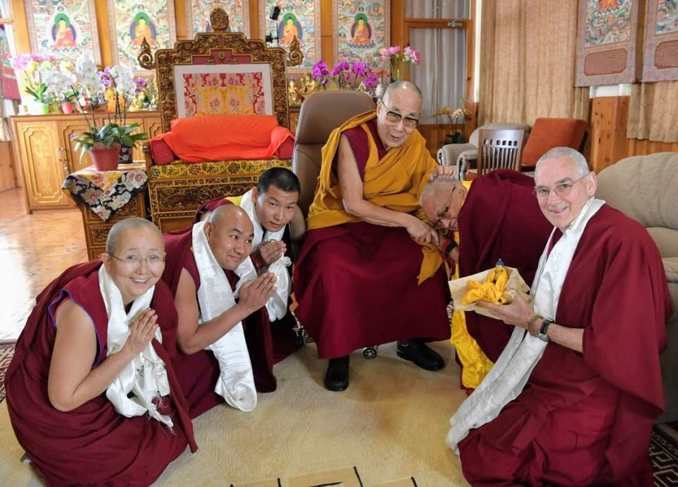 His Holiness the Dalai Lama with Lama Zopa Rinpoche, who is bowed low, with Vens Tsenla, Tendar, Topgy, and Roger kneeling with hands in prostration mudra
