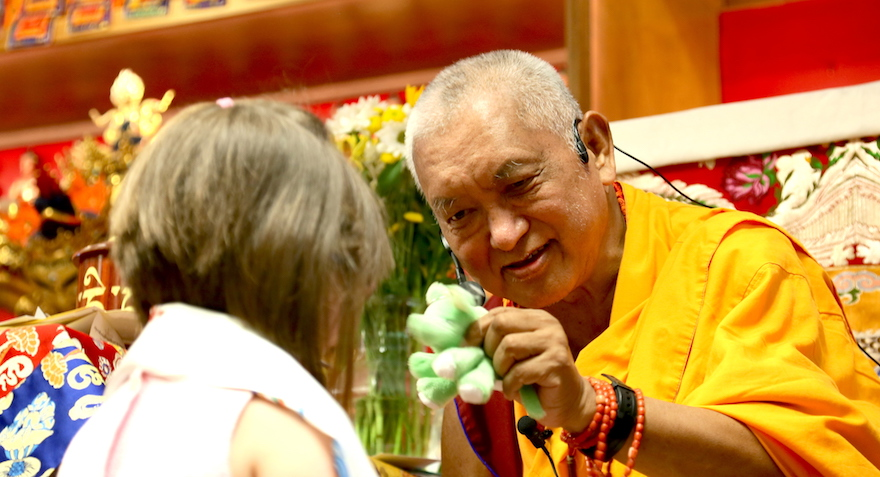 Lama Zopa Rinpoche holding a flower and blessing a child at a teaching event.