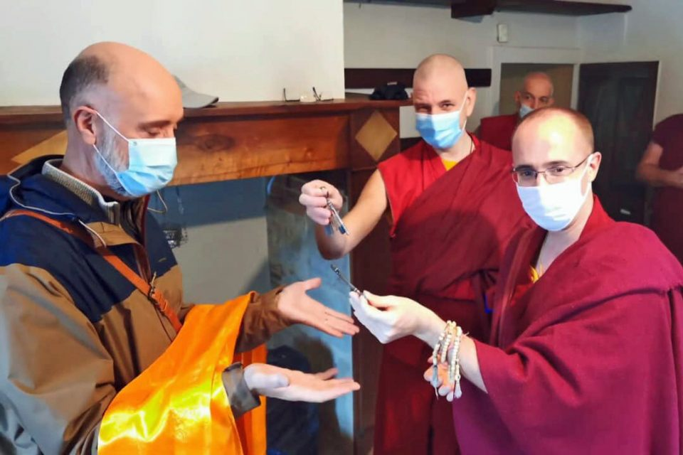 a man wearing a face mask holds a golden colored khata while the two monks wearing face masks hold keys.