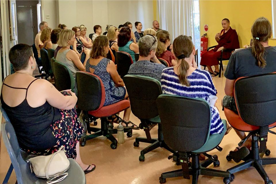 Geshe Tenzin Zopa seated in an office style chair and speaking to a room of people all seated on rolling office chairs.