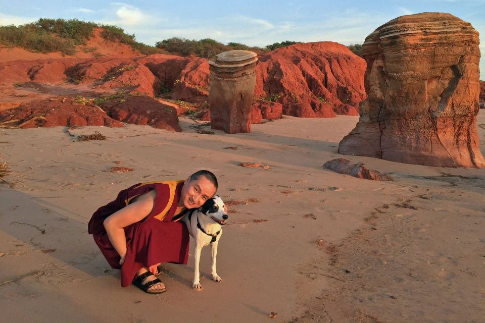 Geshe Tenzin Zopa in a crouched position next to a white and black dog with his arm wrapped around the dog and posing for the camera on a beach.