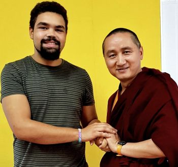 Jacob and Geshe Tenzin Zopa standing together with hands clasped smiling for the camera.