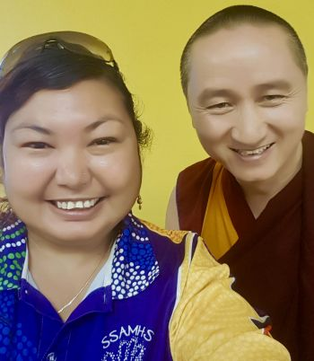Jasmine and Geshe Tenzin Zopa looking into Jasmine's camera as she takes a selfie of the two of them.